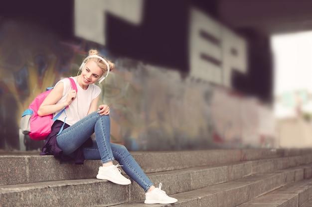 Красивая девушка слушает музыку на улице