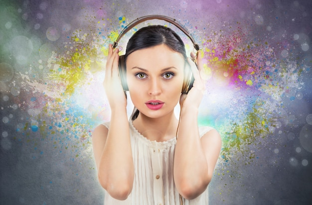 Beautiful girl listening to the music with a pair of headphones