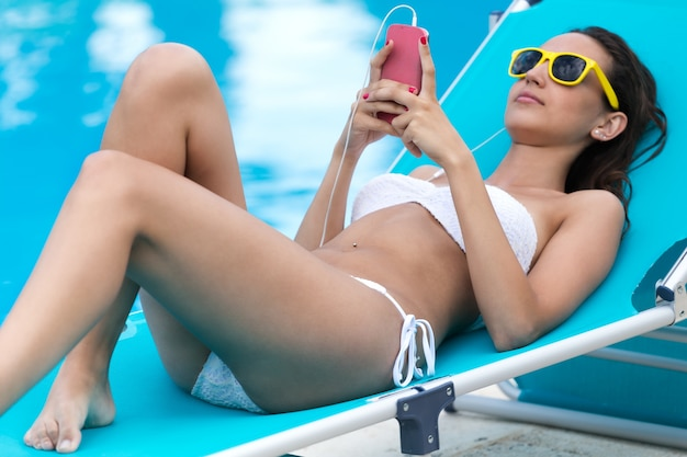 Красивая девушка, слушать музыку в бассейне.