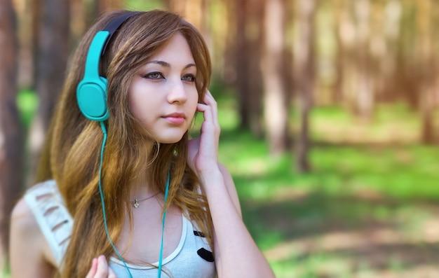 公園でヘッドフォンで音楽を聴いている美しい少女