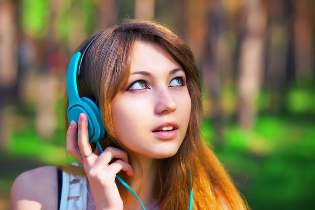 공원에서 헤드폰으로 음악을 듣고 있는 아름다운 소녀
