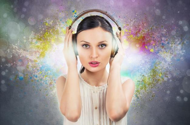 Красивая девушка, слушая музыку с помощью пары наушников