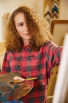 Beautiful girl listens to music via headphones and is drawing a painting with oils