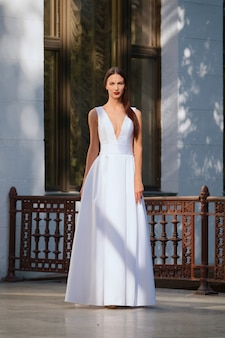 Beautiful girl in long white dress with a deep neckline. fashion model posing on terrace of a palace.