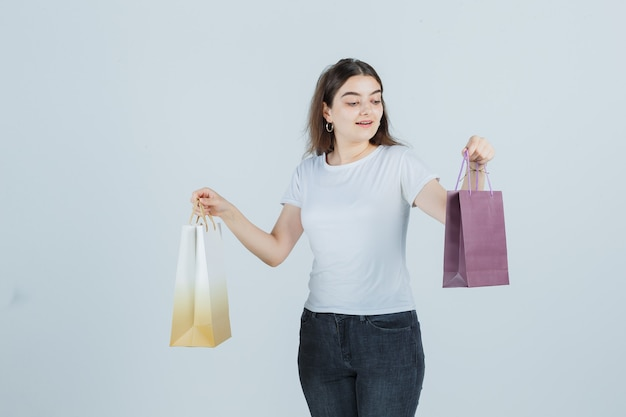 Beautiful girl looking at gift bags in t-shirt, jeans and looking surprised. front view.