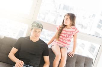 Beautiful girl looking hat her father wearing cap