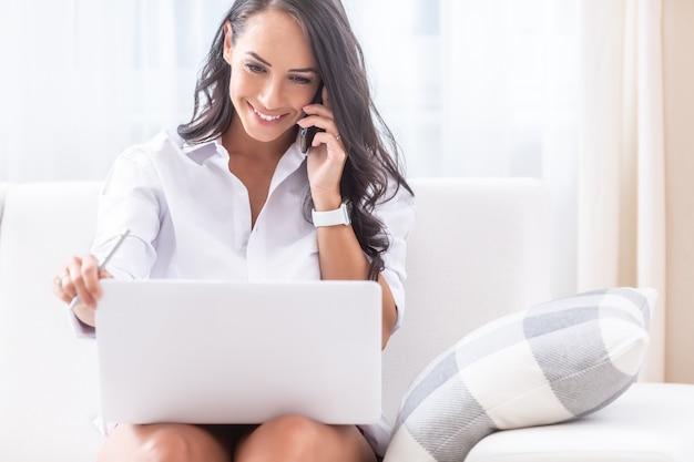 Красивая девушка смотрит в свой ноутбук на коленях, улыбается и держит ручку в правой руке и телефон на ухе левой рукой, сидя на диване в своей светлой квартире.