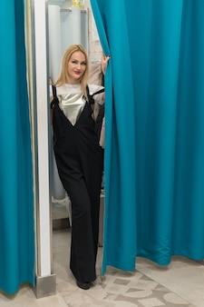 아름 다운 소녀 피팅 룸에서 거울에 드레스를 보인다.