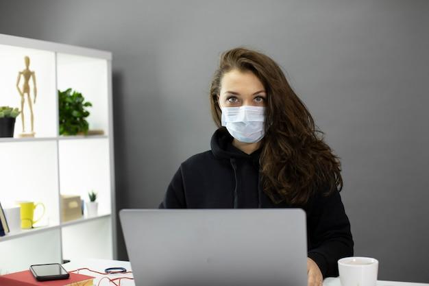아름 다운 소녀는 의료 마스크 작업에서 카메라, 비즈니스 우먼을 심각하게 보인다