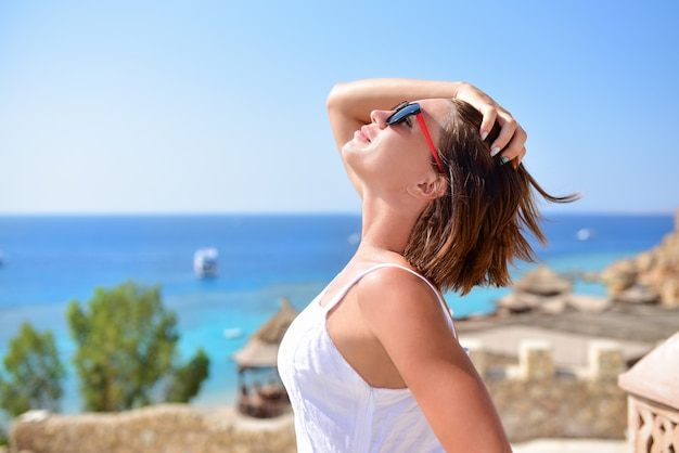 Beautiful girl looks at the sky in the summer resort in summer
