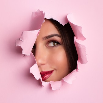 Beautiful girl looks through hole in pink paper background.