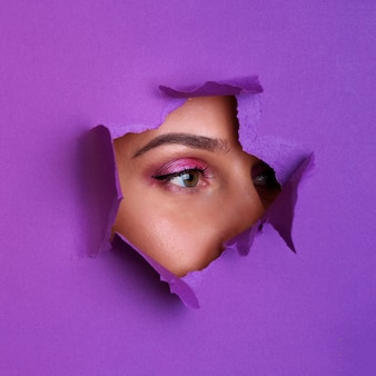 Beautiful girl looks through hole in violet paper background.