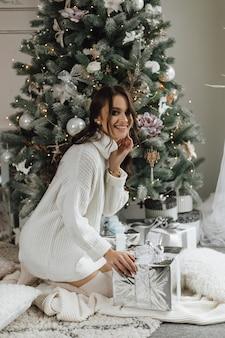 Красивая девушка выглядит очень счастливой и собирается распаковать подарок