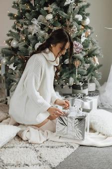 Красивая девушка выглядит очень счастливой и распаковывает подарок на фоне елки