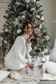 Beautiful girl looks very happy and is going unpack a gift