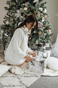 La bella ragazza sembra molto felice e scompatta un regalo su uno sfondo di albero di natale