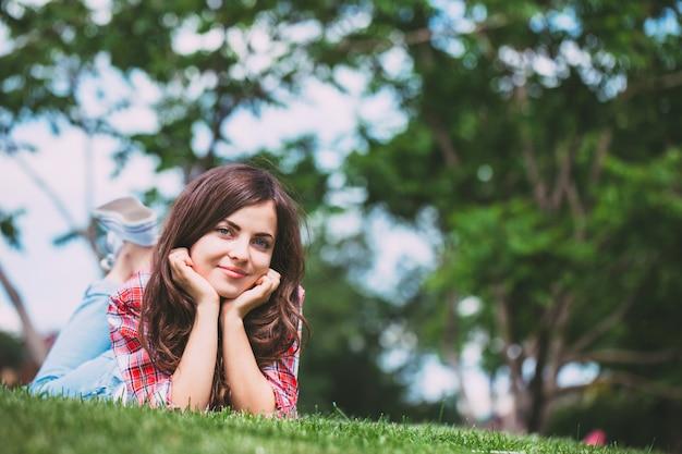 Beautiful girl lying on green grass.