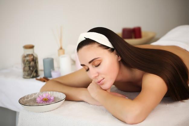 Красивая девушка, лежа на столе, завернутая в полотенце в спа