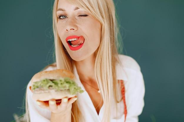 아름다운 소녀는 샐러드를 만듭니다. 부엌에서 스포티 한 금발입니다. 여자는 햄버거와 사과 중에서 선택합니다.