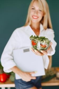 美しい少女はサラダを作ります。キッチンでスポーティなブロンド。手にウェイトを持っている女性。