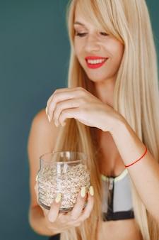 美しい少女はサラダを作ります。キッチンでスポーティなブロンド。オート麦を持つ女性。