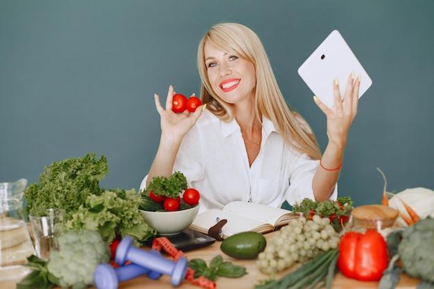 Красивая девушка делает салат. спортивная блондинка на кухне. рецепт сочинительства женщины в тетради.