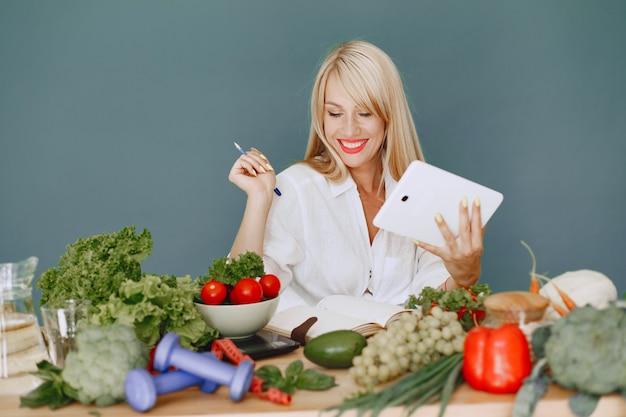 La bella ragazza fa un'insalata. bionda sportiva in cucina. ricetta di scrittura della donna in taccuino.