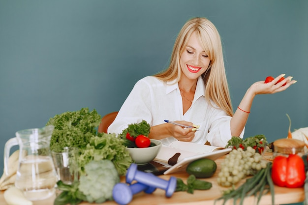 Beautiful girl make a salad. sporty blonde in a kitchen. woman writing recipe in notebook.