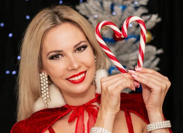 美しい少女は赤と白のクリスマスのお菓子で心を作る