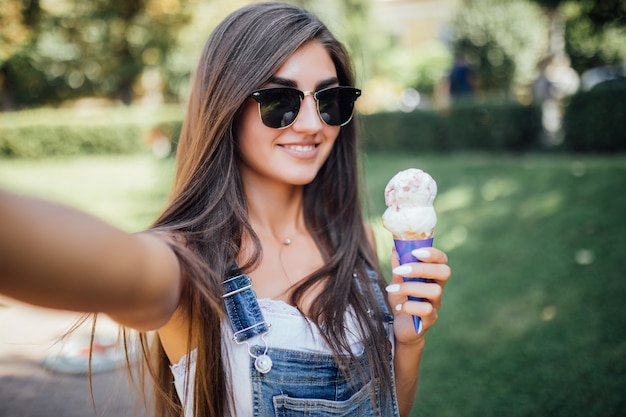 Beautiful girl makes selfie smiles with white teeth and holds the ice cream wearing sunglasses