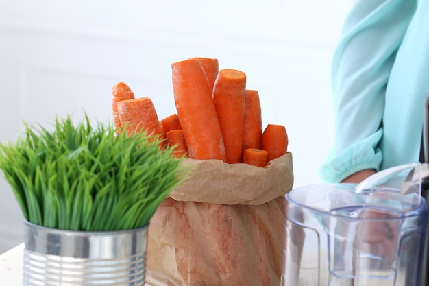 Beautiful girl making carrot juice