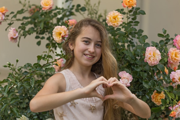 Beautiful girl making heart shape with her hands, outside during daytime .