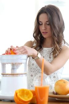 Beautiful girl making orange juice