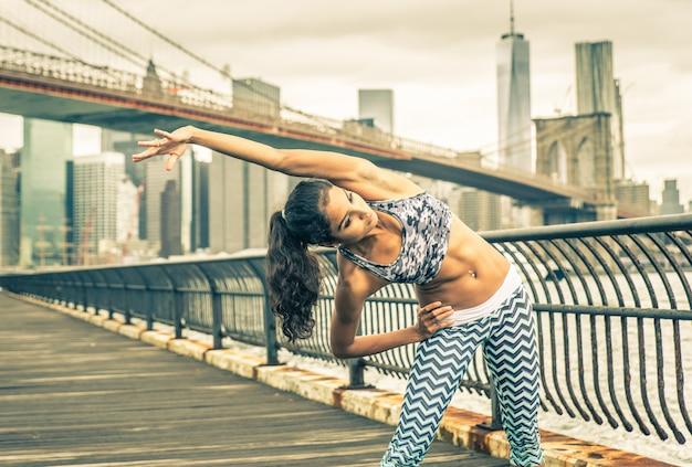 ニューヨーク市で激しいランニングの前にストレッチを作る美しい少女
