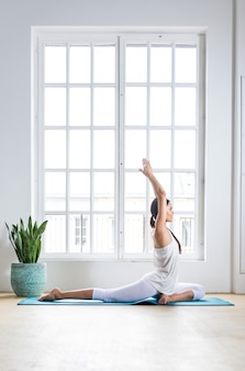 Beautiful girl making training and yoga at home in the morning