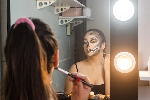 Красивая девушка делает художественный череп на хэллоуин в своей комнате.