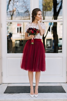 Beautiful girl in marsala tulle skirt on heels walking on street. she holds boquet of  flowers and smiling to side
