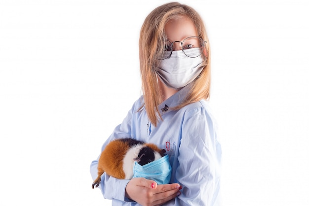 Beautiful girl in a medical mask and glasses is holding guinea pig in a protective mask in her hands on light grey