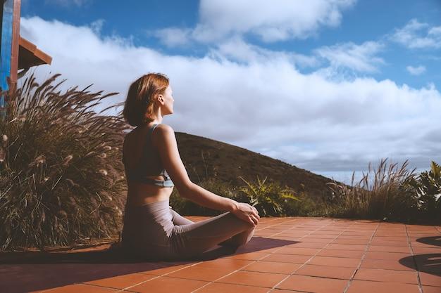 Красивая девушка медитирует и делает расслабляющие дыхательные упражнения на террасе дома