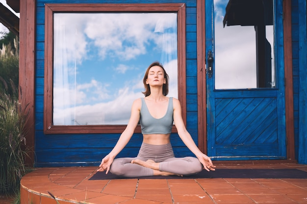 Beautiful girl meditating and doing relaxing breathing exercise on terrace of home