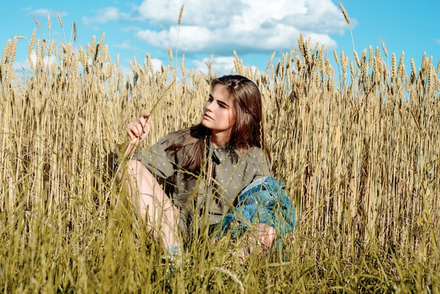 Beautiful girl model in dress in the countryside. against the background of a field among wheat. blue sky, freedom and hot summer concept.