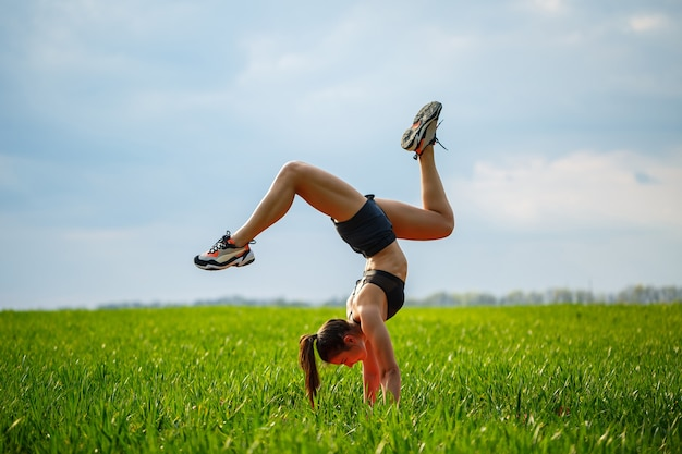 Beautiful girl model on green grass do yoga. a beautiful young woman on a green lawn performs acrobatic elements. flexible gymnast in black does a handstand in split