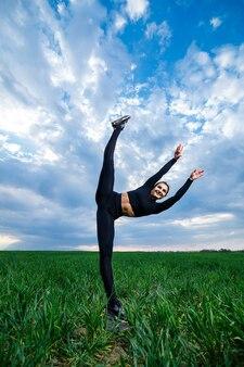 Красивая девушка-модель на зеленой траве занимается йогой. красивая брюнетка на зеленой лужайке выполняет акробатические элементы. гибкая гимнастка в черном делает упражнения