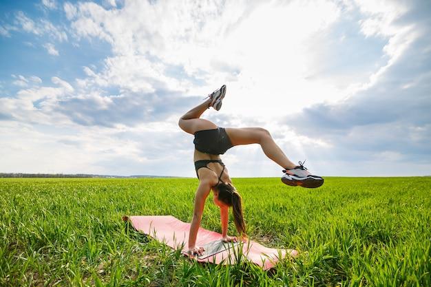 Красивая девушка-модель на зеленой траве занимается йогой. красивая молодая женщина на зеленой лужайке выполняет акробатические элементы. гибкая гимнастка в черном делает стойку на руках в шпагате