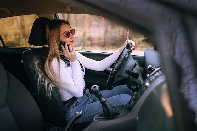 Красивая девушка модель сидит в машине и разговаривает по мобильному телефону