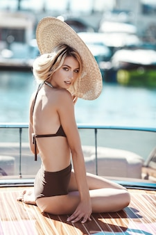 A beautiful girl, a model in a swimsuit and a wide-brimmed hat