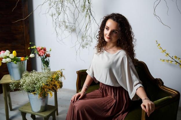 Красивая девушка модель с локонами в платье позирует в красивых аранжировках. начало весны с цветами