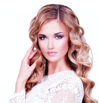 長いブロンドの巻き毛を持つ美しい少女モデル。明るいアイメイクで官能的な女性。白い壁に隔離。