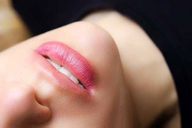 女の子の永続的な唇のメイクの目に見える音を持つ美しい女の子モデル