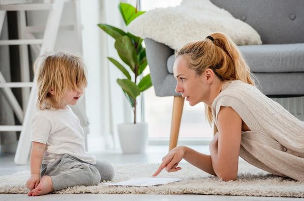 아름다운 소녀 어머니는 그녀의 아들과 함께 그림을 그리고 그에게 그림을 그리는 방법을 설명합니다